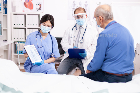 Healthcare physician explaining human anatomy to senior man - Stock Photo - Images