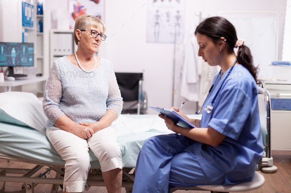 Nurse writing prescription on clipboard - Stock Photo - Images