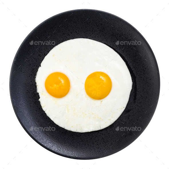 top view of fried eggs on black plate isolated - Stock Photo - Images