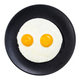 top view of fried eggs on black plate isolated - PhotoDune Item for Sale