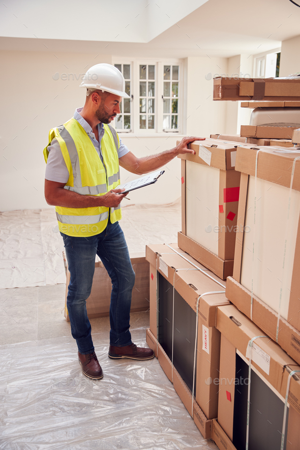 Builder Wearing Hard Hat With Clipboard Checking Delivery Of New Kitchen Units Inside Property - Stock Photo - Images