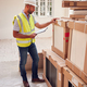 Builder Wearing Hard Hat With Clipboard Checking Delivery Of New Kitchen Units Inside Property - PhotoDune Item for Sale