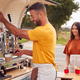 Couple Running Independent Mobile Coffee Shop Preparing Drink Standing Outdoors Next To Van - PhotoDune Item for Sale
