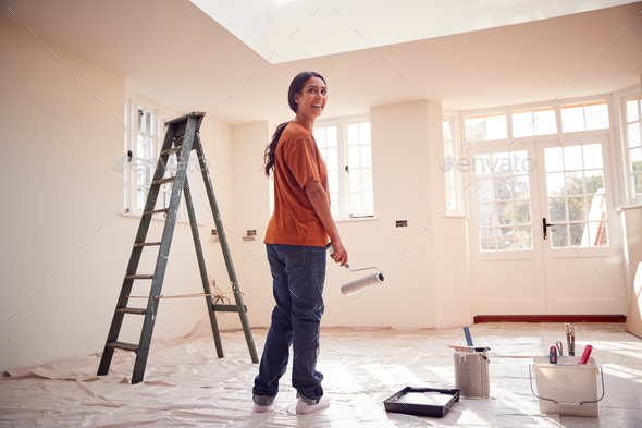 Rear View Of Woman With Paint Roller Decorating New Home - Stock Photo - Images