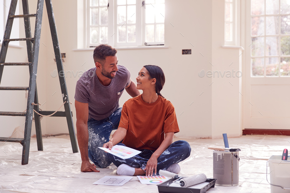 Couple Sitting On Floor With Paint Chart Ready To Decorate New Home - Stock Photo - Images