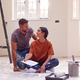 Couple Sitting On Floor With Paint Chart Ready To Decorate New Home - PhotoDune Item for Sale
