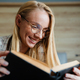 Beautiful blonde pleased woman reading book while lying in bed - PhotoDune Item for Sale
