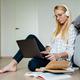 Blonde focused woman in headphones using laptop while sitting on floor - PhotoDune Item for Sale