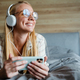 Blonde smiling woman listening music with earphones and mobile phone - PhotoDune Item for Sale