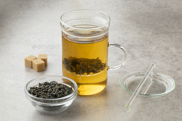 Tea glass with green gunpowder tea and a bowl with dried tea leaves - Stock Photo - Images