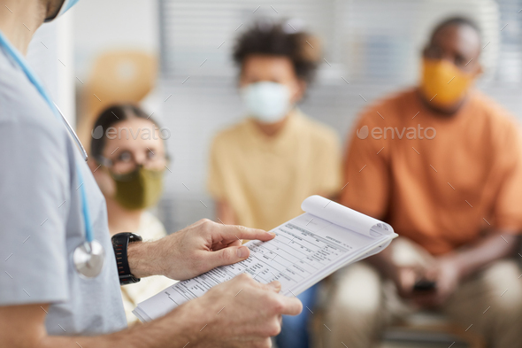 Male Nurse Checking Vaccination Chart - Stock Photo - Images