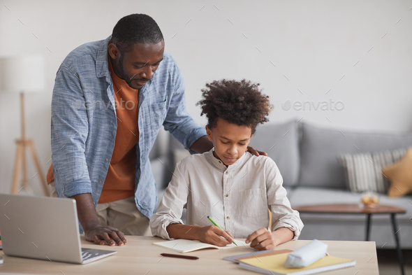 Father Helping Son Doing Homework - Stock Photo - Images