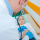 Doctor Examining His Small Patient on Hospital Bed. - PhotoDune Item for Sale