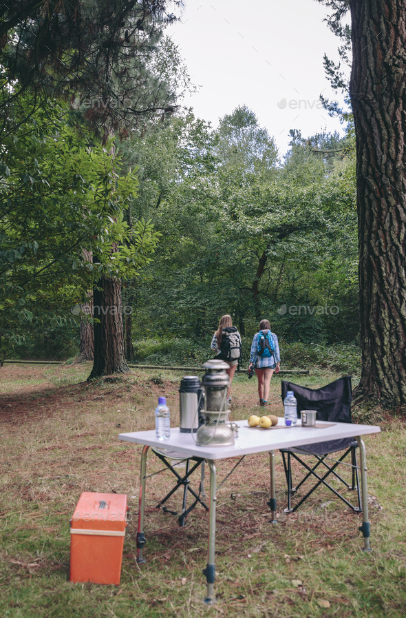 Women hiking with camping table in foreground - Stock Photo - Images