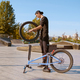 Young male bmx biker adjusts his bike in skatepark - PhotoDune Item for Sale