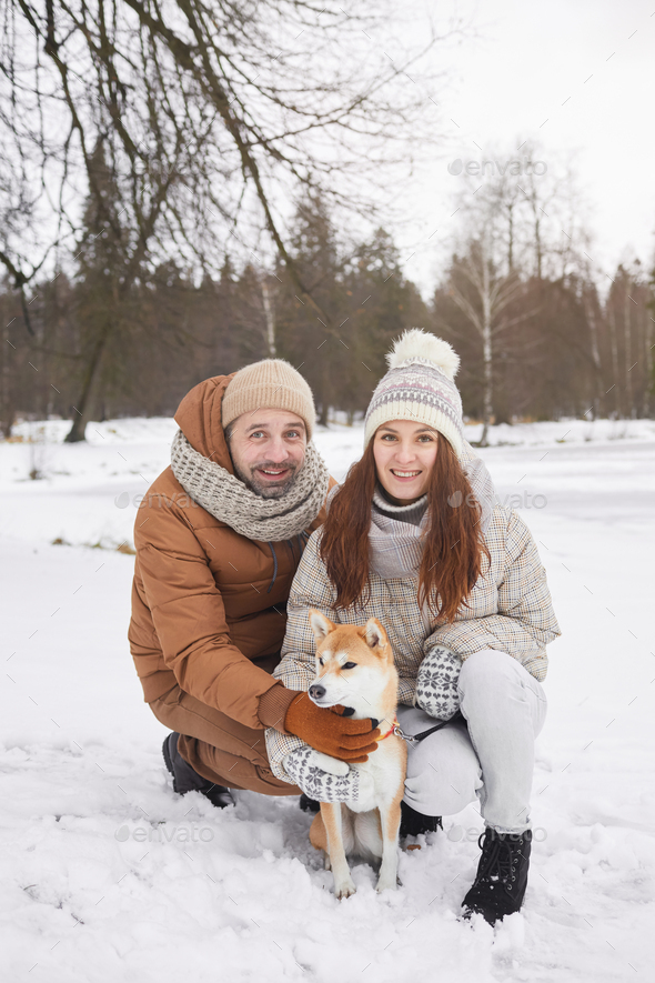 Smiling Couple Posing with Dog in Winter - Stock Photo - Images