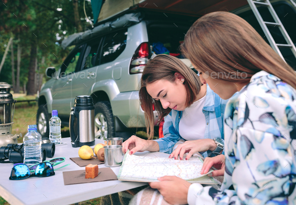 Young women looking road map with 4x4 on background - Stock Photo - Images