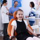 Cheerful kid sitting on chair in dentist office during visit for bad tooth treatment - PhotoDune Item for Sale