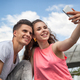 Young couple sitting in town outdoor with mobile phone taking selfie - PhotoDune Item for Sale
