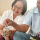 Elderly couple put coins in a glass jar to save money. - PhotoDune Item for Sale