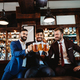 Handsome businessmen are drinking beer, talking and smiling while resting at the pub - PhotoDune Item for Sale