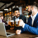 Happy young businessmen drinking beer and talking at pub after work - PhotoDune Item for Sale