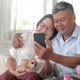 Senior husband and wife use smartphone for video calling in the house with chihuahua dog. - PhotoDune Item for Sale