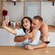 Couple together in the kitchen at morning time with mobile phone - PhotoDune Item for Sale