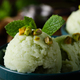 Pistachio icecream balls in clay bowls on wooden kitchen table with crumbs and nuts aside - PhotoDune Item for Sale