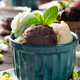 Three scoops of Vanilla pistachio and chocolate icecream balls in clay bowls on wooden kitchen table - PhotoDune Item for Sale