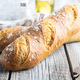 Two crispy fresh baguettes on wooden table. - PhotoDune Item for Sale