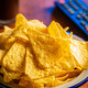 Salted tortilla chips. Yellow nachos triangle and tv remote control - PhotoDune Item for Sale