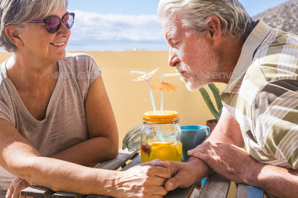 Senior happy couple enjoy together an orange juice having fun in outdoor sitting at the table - Stock Photo - Images