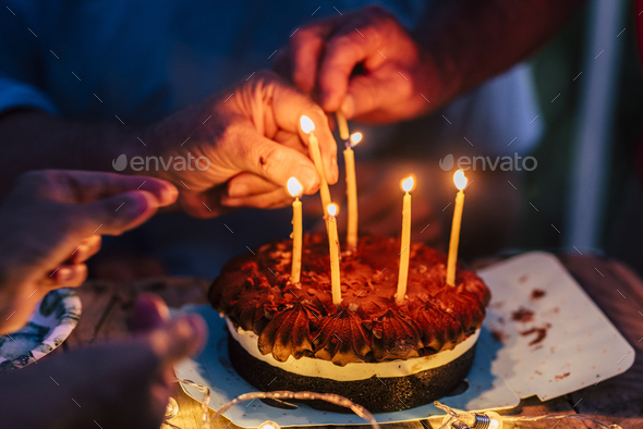 Close up of people hands fire candles on a birthday celebration cake on the table - Stock Photo - Images