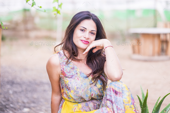 Beautiful young woman posing with coloured dress outdoor smiling at the camera - Stock Photo - Images