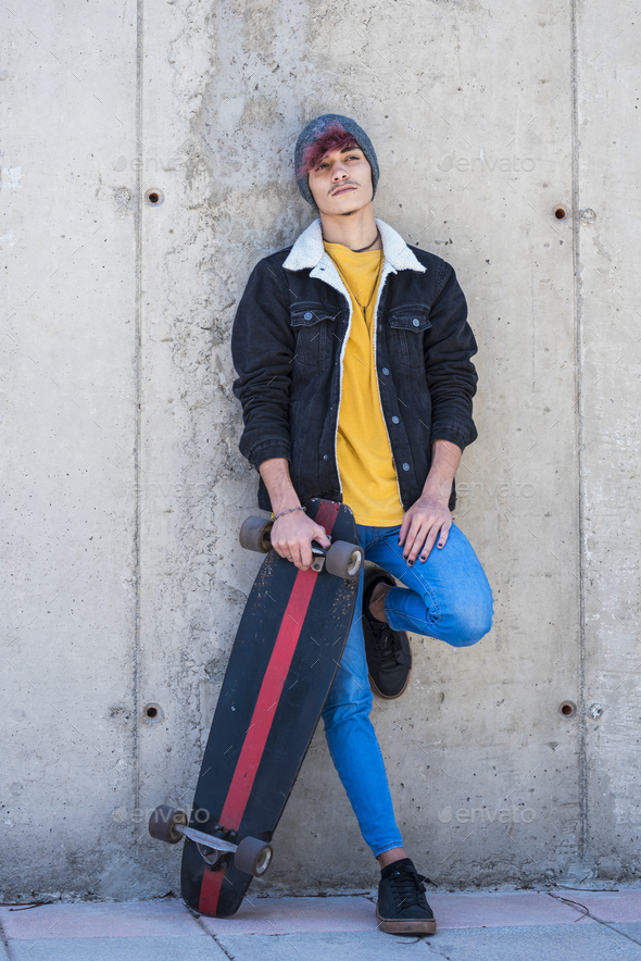 Portrait of young and alternative boy standing with skate board and colorful clothes - modern people - Stock Photo - Images