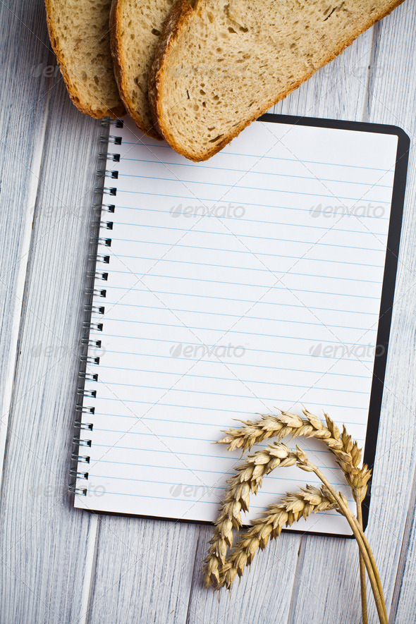 blank notebook with bread and wheat - Stock Photo - Images