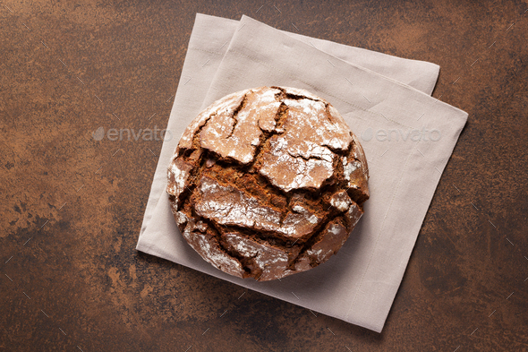 Loaf of fresh bread on napkin cloth at table - Stock Photo - Images