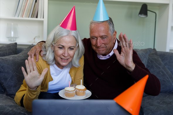 Senior caucasian couple celebrating birthday while having a video chat on laptop at home - Stock Photo - Images