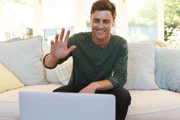 Caucasian man having video call waving and smiling to laptop in living room - Stock Photo - Images