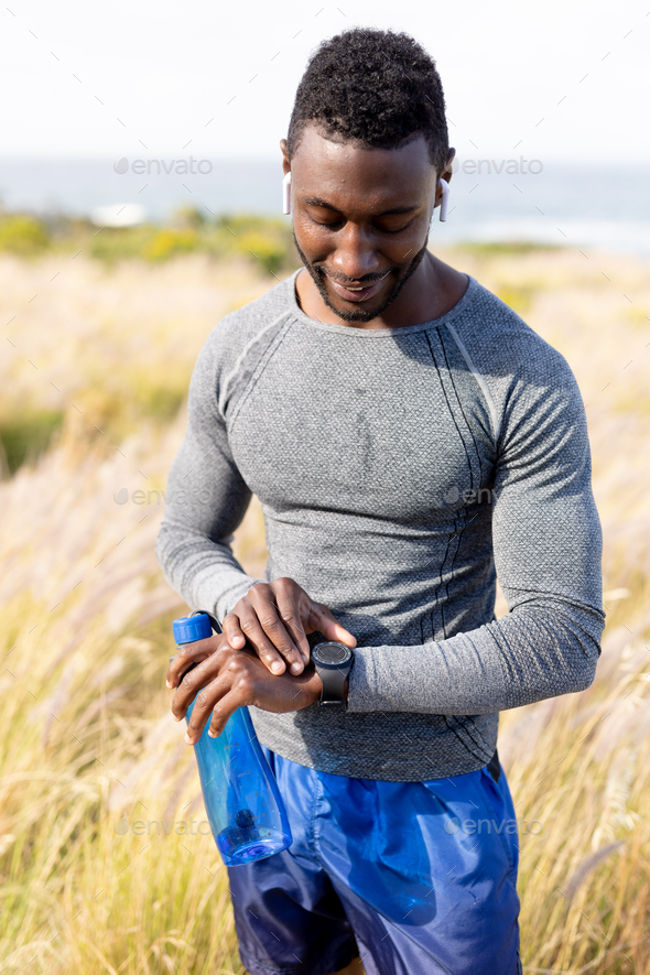 Portrait of fit african american man in sportswear using smartwatch holding water in tall grass - Stock Photo - Images