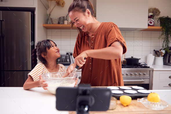 Asian Mother And Daughter Baking Cupcakes In Kitchen At Home Whilst On Vlogging On Mobile Phone - Stock Photo - Images