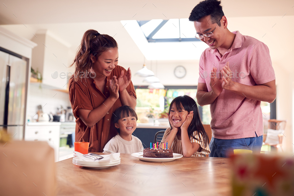 Asian Family Celebrating Daughters Birthday At Home Surprising Him With Candle Covered Cake - Stock Photo - Images