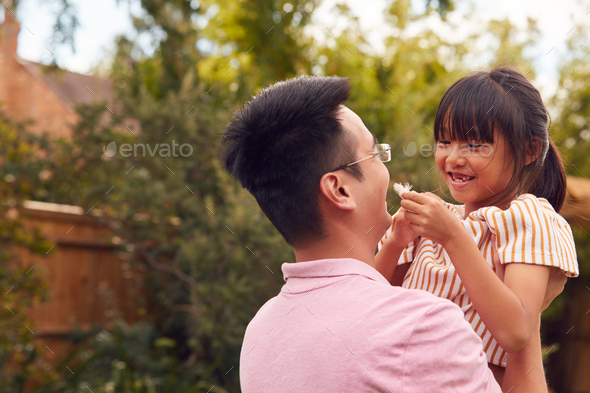 Asian Father Lifting Daughter In Mid Air As They Play Game In Garden Together - Stock Photo - Images