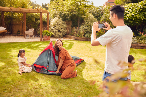 Asian Father Taking Photo On Mobile Phone As  Put Up Tent Family In Garden At Home - Stock Photo - Images