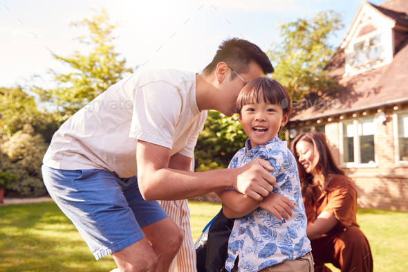 Asian Family Having Fun In Summer Garden At Home With Children Playing Together - Stock Photo - Images