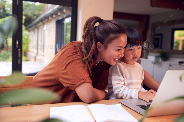Asian Mother Helping Home Schooling Son Working At Table In Kitchen On Laptop - Stock Photo - Images