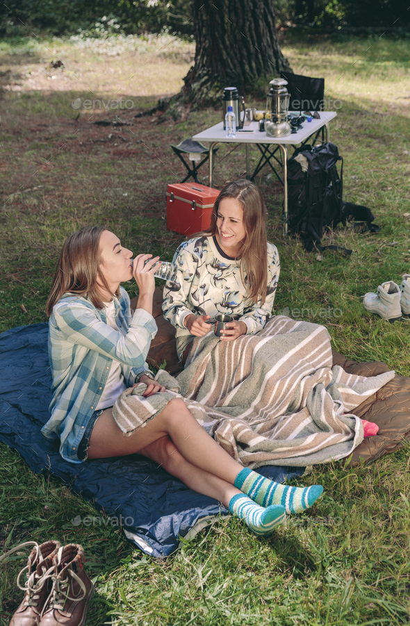 Woman drinking water with friend in campsite - Stock Photo - Images