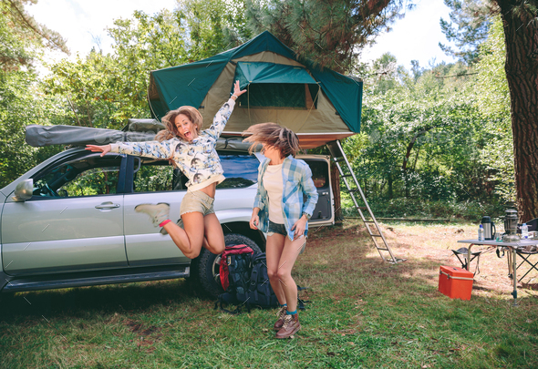 Young women having fun in campsite with 4x4 on background - Stock Photo - Images