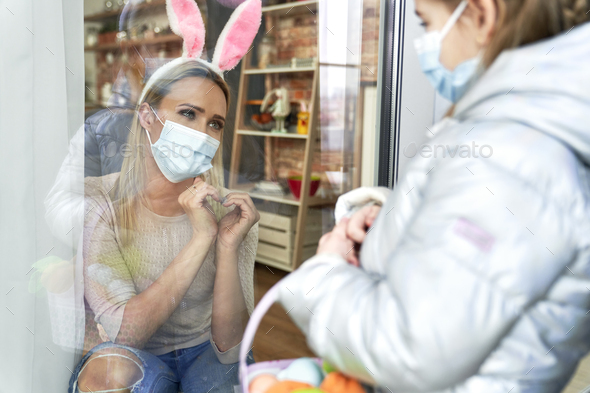 Mother sending heart to her daughter during Easter quarantine - Stock Photo - Images